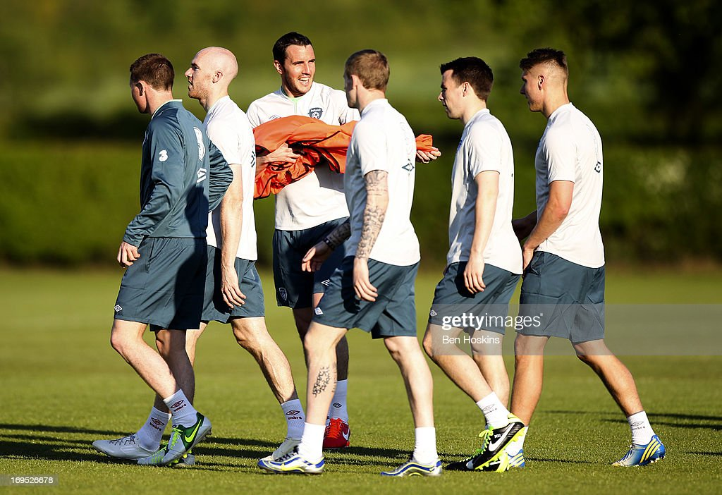 John O'Shea (3rd L) of the Republic of Ireland hands out bibs to squad members during an Ireland training session at Watford FC Training Ground on May 26, 2013 near St Albans, London Colney, England.
