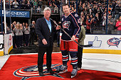 John P McConnell majority owner of the Columbus Blue Jackets presents a silver stick to Scott Hartnell in recognition for playing 1000 games in the...