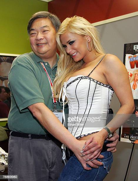 John Pang from Movietime Video takes a photo with adult film actress Shyla Stylez at the Brazzers booth at the 2008 AVN Adult Entertainment Expo and...