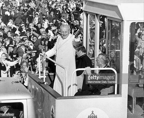 John Paul II in his 'Popemobile' waves to the huge crowds who turned out greet him during his visit to Ireland
