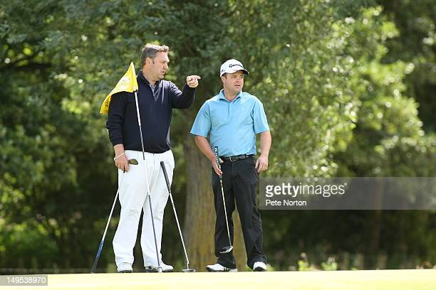 John Peters of Southerndown Golf Club makes a point to Glenn Howells at the 1st green during the Virgin Atlantic PGA National ProAm Championship...