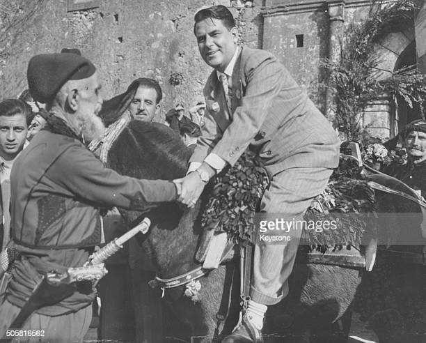 John Peurifoy the new US Ambassador to Greece pictured shaking hands with an old Cretan soldier as he sits on the back of a mule during his tour of...