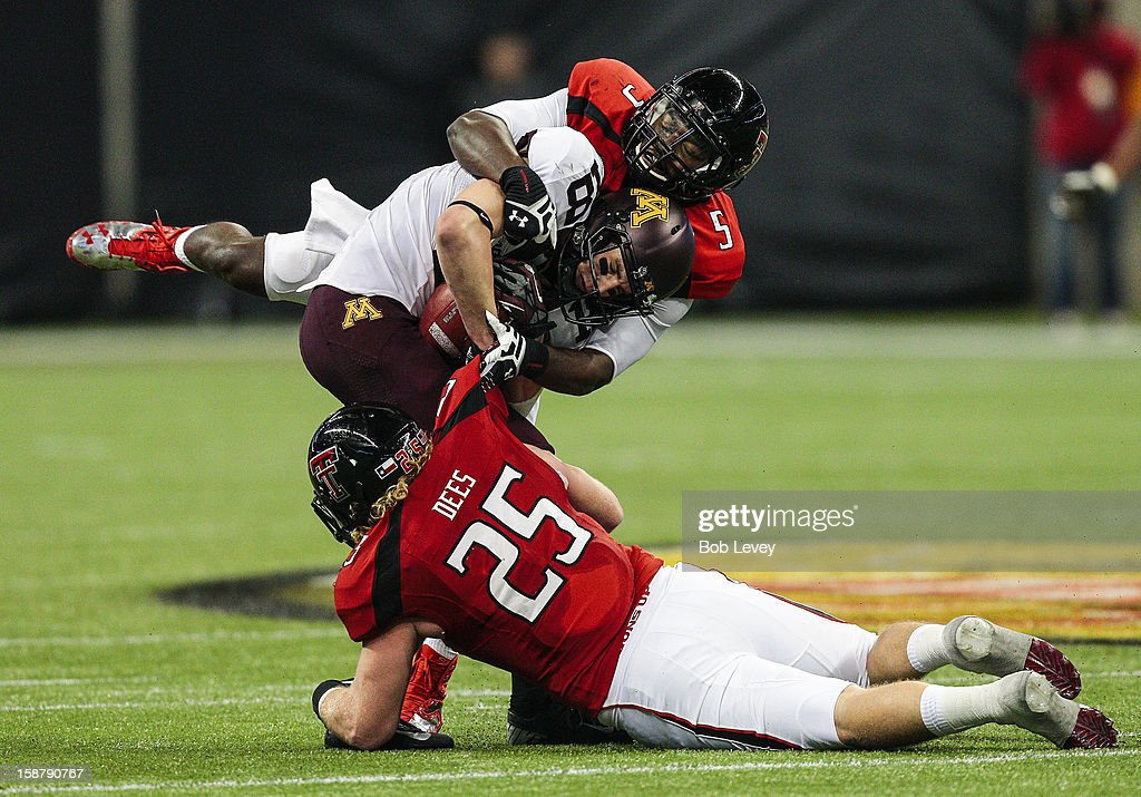 John Rabe #81 of the Minnesota Golden Gophers is tackled by Blake Dees #25 of the Texas Tech Red Raiders and Tre' Porter #5 of the Texas Tech Red Raiders during the Meineke Car Care of Texas Bowl at Reliant Stadium on December 28, 2012 in Houston, Texas. Texas Tech defeated Minnesota 34-31.