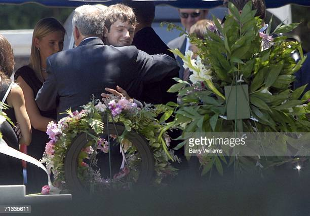 John Ramsey hugs his son Burke at the grave of JonBenet Ramsey after graveside service for his wife Patsy Ramsey June 29 2006 in Marietta Georgia...