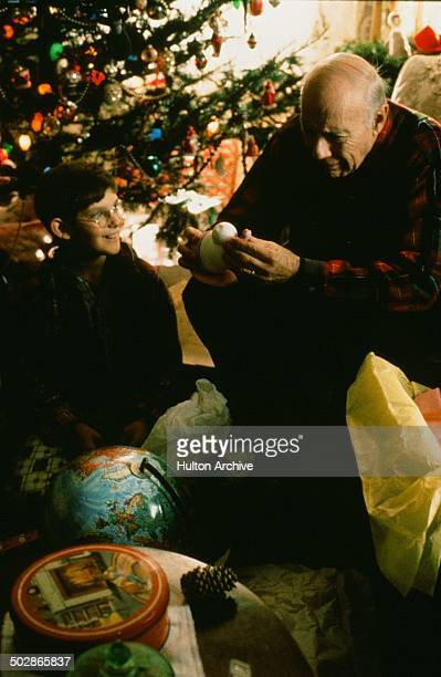 John Randolph opens a Christmas gift from Lukas Haas in a scene from the movie 'The Wizard of Loneliness' circa 1988