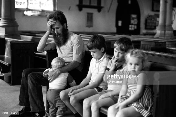 John Reynolds a friend of massacre victim PC Roger Brereton prays with his family at the church of St Lawrence Hungerford