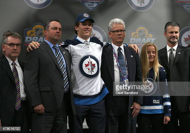 John Roslovic poses for a group photo with members of the Winnipeg Jets organization after being selected 25th overall by the Winnipeg Jets during...