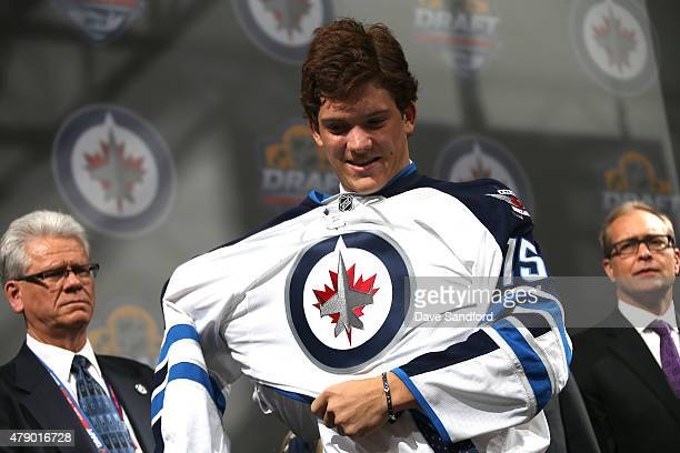 John Roslovic puts on a jersey onstage after being selected 25th overall by the Winnipeg Jets during Round One of the 2015 NHL Draft at BBT Center on...