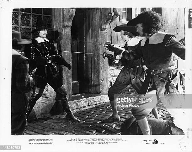 John Russell raising gun at swordsmen in a scene from the film 'Forever Amber' 1947