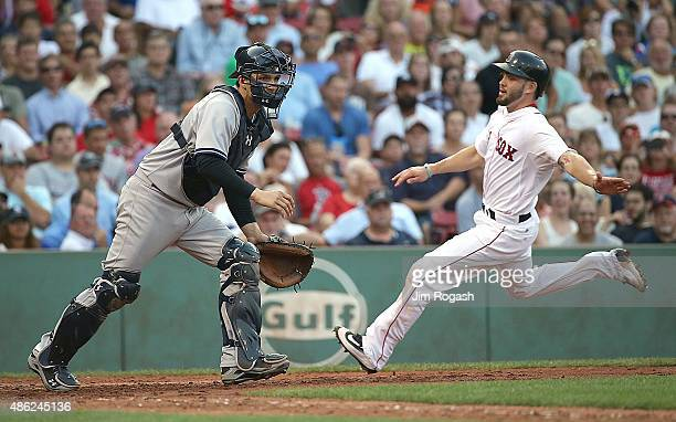 John Ryan Murphy of the New York Yankees awaits a late throw to the plate as Blake Swihart of the Boston Red Sox scores in the fifth inning against...