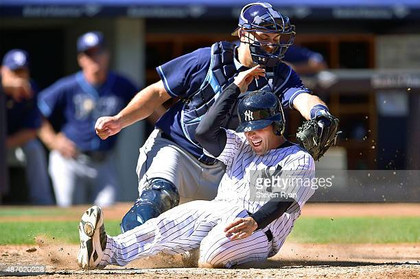 John Ryan Murphy of the New York Yankees slides in safely to score a run in the fifth inning past the tag of Luke Maile of the Tampa Bay Rays at...