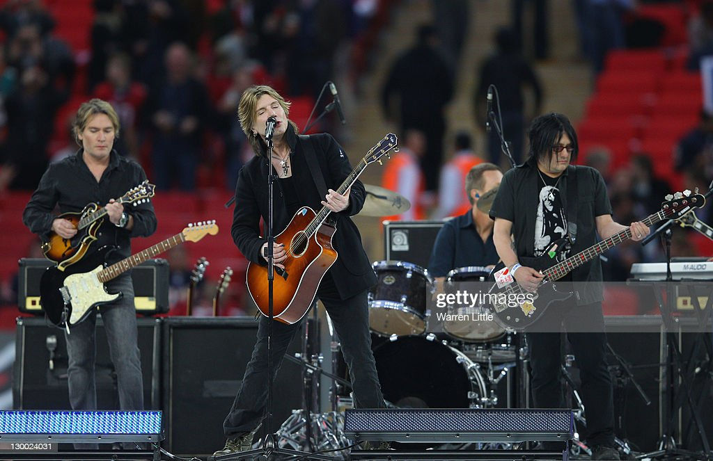John Rzeznik (C) and Robby Takac (R) of the Goo Goo Dolls perform the pregame entertainment prior to the NFL International Series match between Chicago Bears and Tampa Bay Buccaneers at Wembley Stadium on October 23, 2011 in London, England. This is the fifth occasion where a regular season NFL match has been played in London.