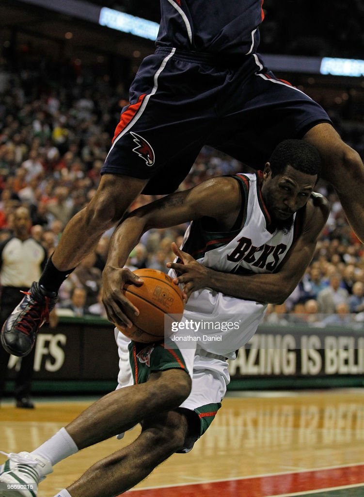 John Salmons of the Milwaukee Bucks ducks under a leaping Al Horford of the Atlanta Hawks as he drives to the basket in Game Four of the Eastern...