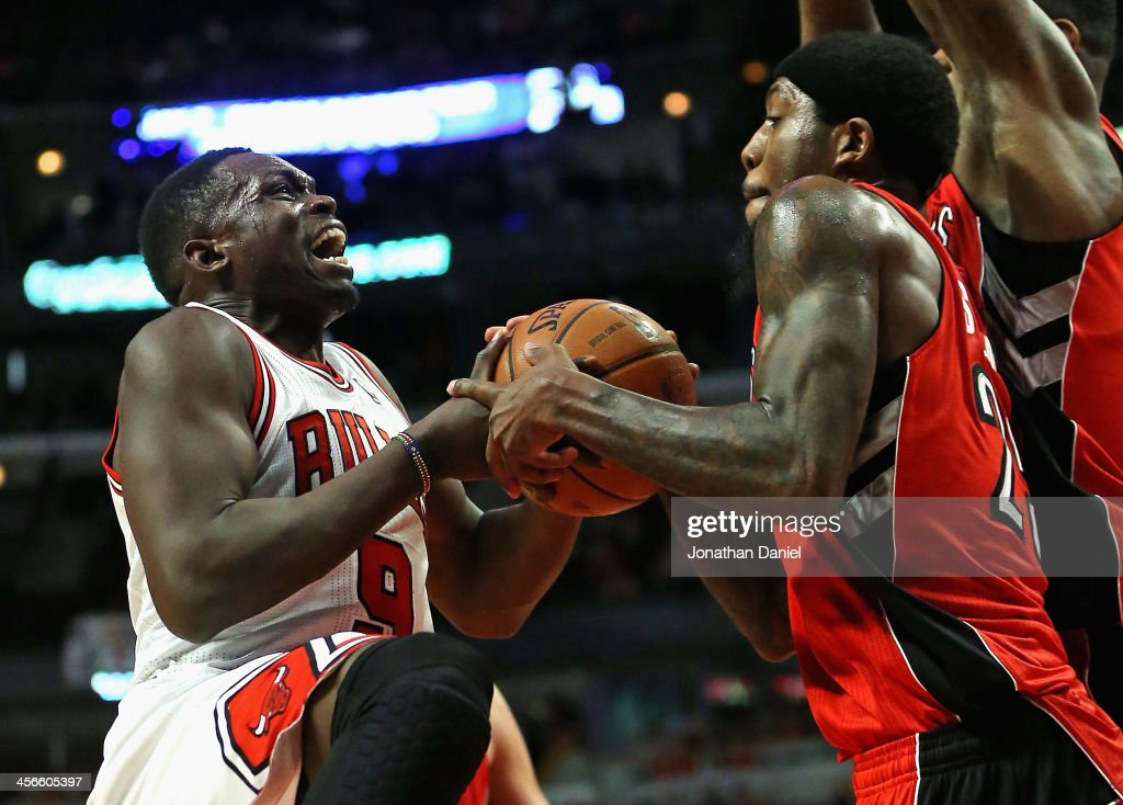 John Salmons of the Toronto Raptors forces a jump ball with Loul Deng of the Chicago Bulls at the United Center on December 14 2013 in Chicago...