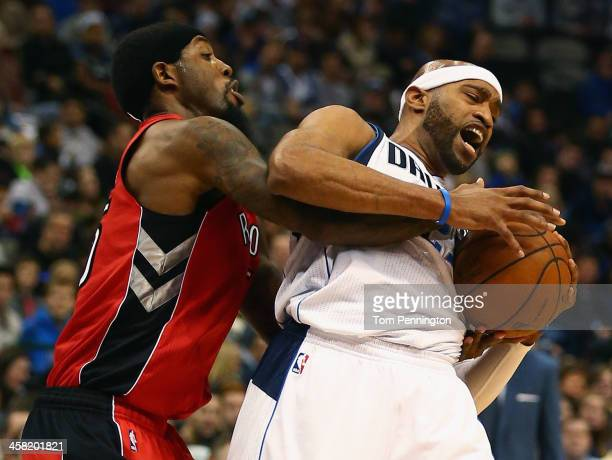 John Salmons of the Toronto Raptors scrambles for the ball against Vince Carter of the Dallas Mavericks at American Airlines Center on December 20...