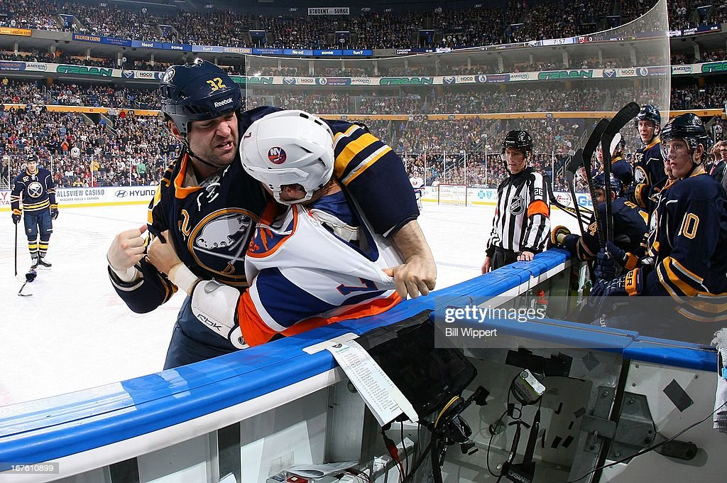 John Scott #32 of the Buffalo Sabres and Matt Carkner #7 of the New York Islanders fight during the second period on April 26, 2013 at the First Niagara Center in Buffalo, New York.