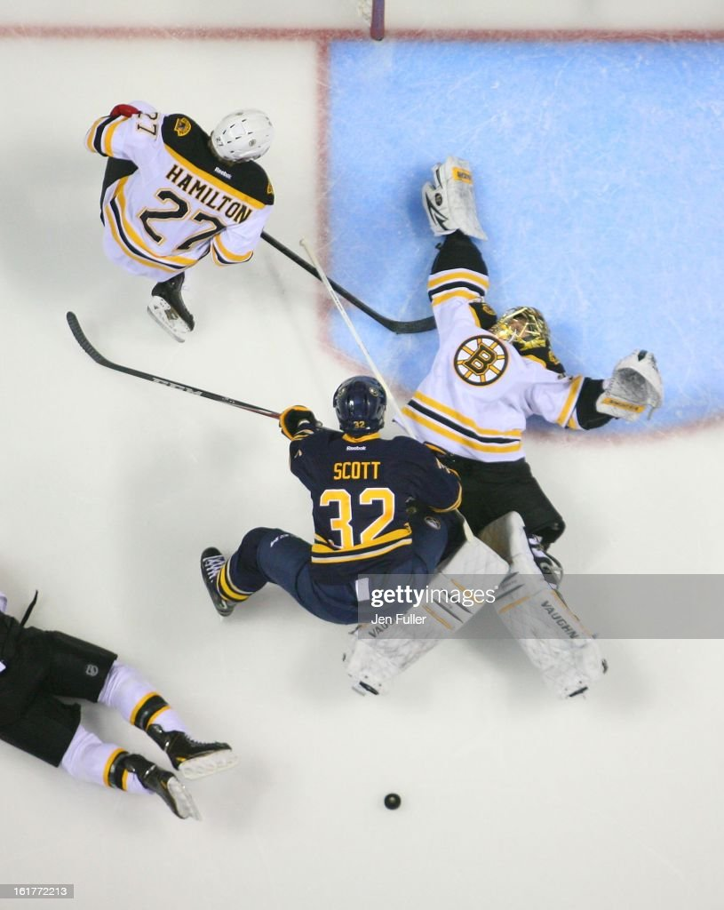 John Scott #32 of the Buffalo Sabres collides with goaltender Anton Khudobin #35 of the Boston Bruins as Dougie Hamilton #27 of the Boston Bruins looks for the puck on February 15, 2013 at the First Niagara Center in Buffalo, New York.