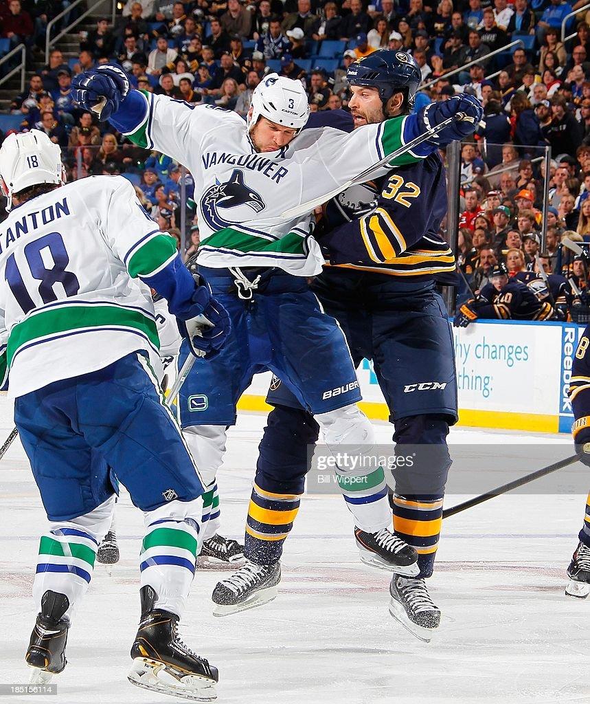 John Scott #32 of the Buffalo Sabres collides with <a gi-track='captionPersonalityLinkClicked' href=/galleries/search?phrase=Kevin+Bieksa&family=editorial&specificpeople=688792 ng-click='$event.stopPropagation()'>Kevin Bieksa</a> #3 of the Vancouver Canucks on October 17, 2013 at the First Niagara Center in Buffalo, New York. Vancouver won, 3-0.