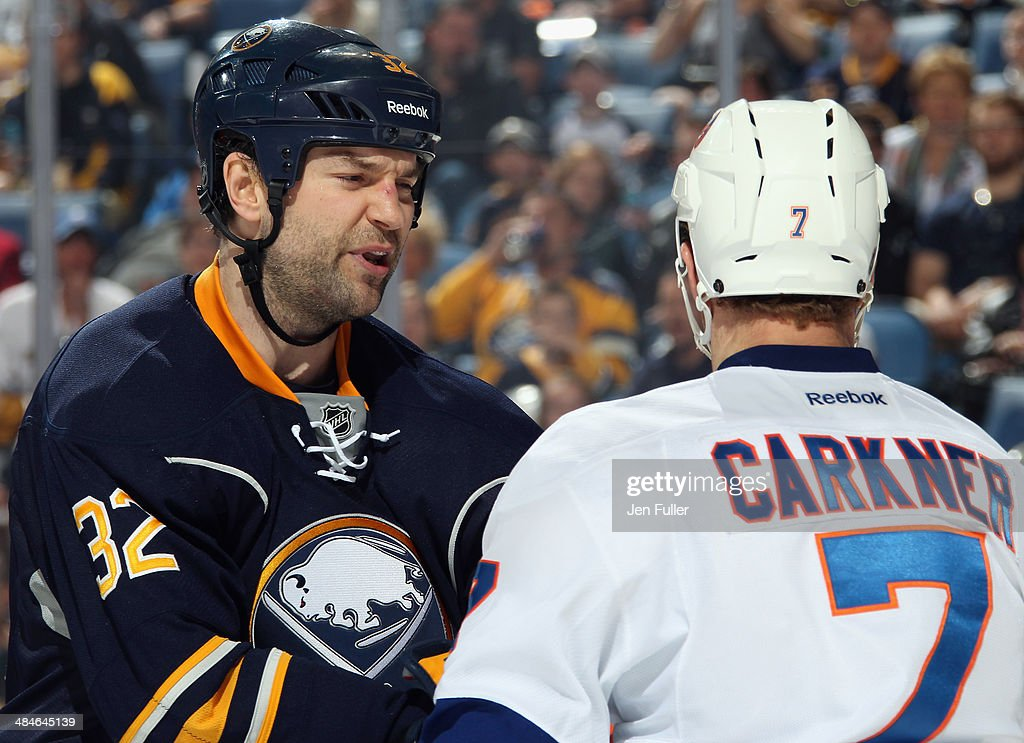 John Scott #32 of the Buffalo Sabres has words with Matt Carkner #7 of the New York Islanders at First Niagara Center on April 13, 2014 in Buffalo, New York.
