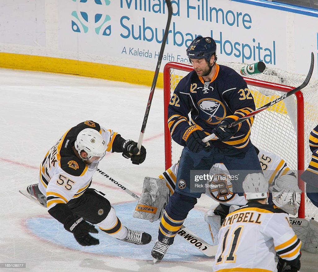 John Scott #32 of the Buffalo Sabres knocks Johnny Boychuk #55 of the Boston Bruins off his feet in the first period at First Niagara Center on March 31, 2013 in Buffalo, New York.