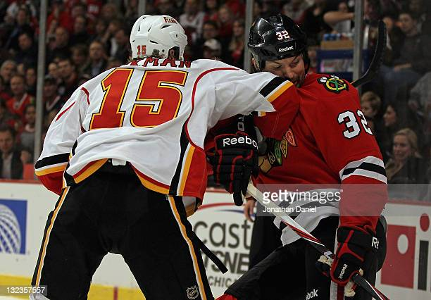 John Scott of the Chicago Blackhawks takes an elbow to the face from Tim Jackman of the Calgary Flames at the United Center on November 11 2011 in...
