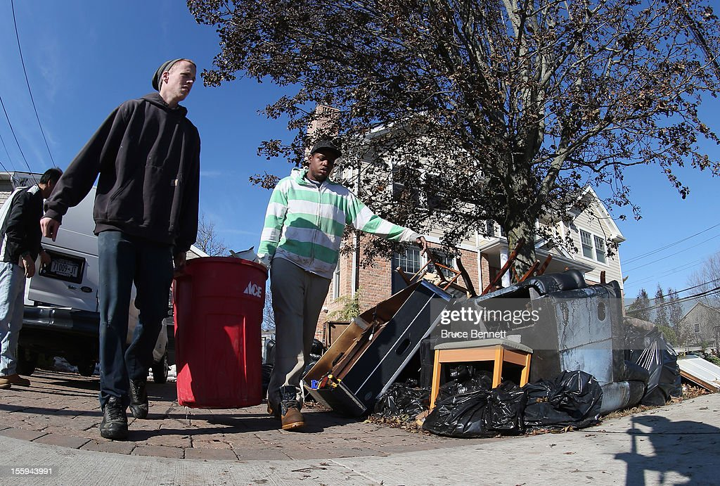 John Seridge and Karl Downie help clean out a home on Beverley Way as residents continue recovery efforts in the aftermath of Superstorm Sandy on November 9, 2012 in Merrick, New York. New York Gov. Andrew M. Cuomo has said that the economic loss and damage to homes and businesses caused by Sandy could total $33 billion in New York, according to published reports.
