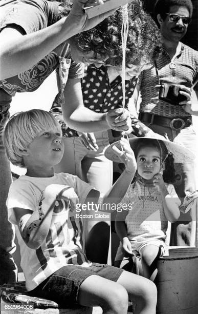 John Shehan 5 1/2 learns macrame from Joy Silverstine while Vanessa Wesley watches wearing a homemade hat during a Summerthing event in Boston on Aug...