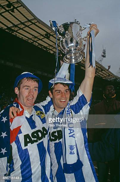 John Sheridan and American soccer player John Harkes of Sheffield Wednesday with the trophy after their team beat Manchester United 10 to win the...
