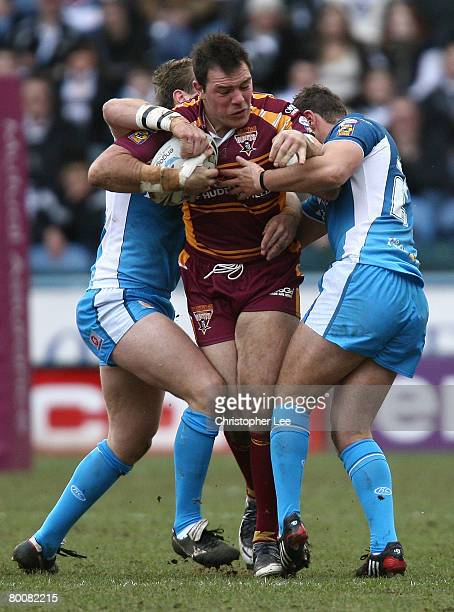 John Skandalis of Huddersfield takes on Ewan Dowes and Tommy Lee of Hull during the Engage Super League match between Huddersfield Giants and Hull FC...