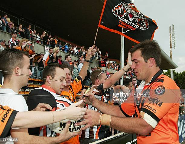 John Skandalis of the Tigers signs a football for a fan after playing his last match after the round 26 NRL match between the Wests Tigers and the...