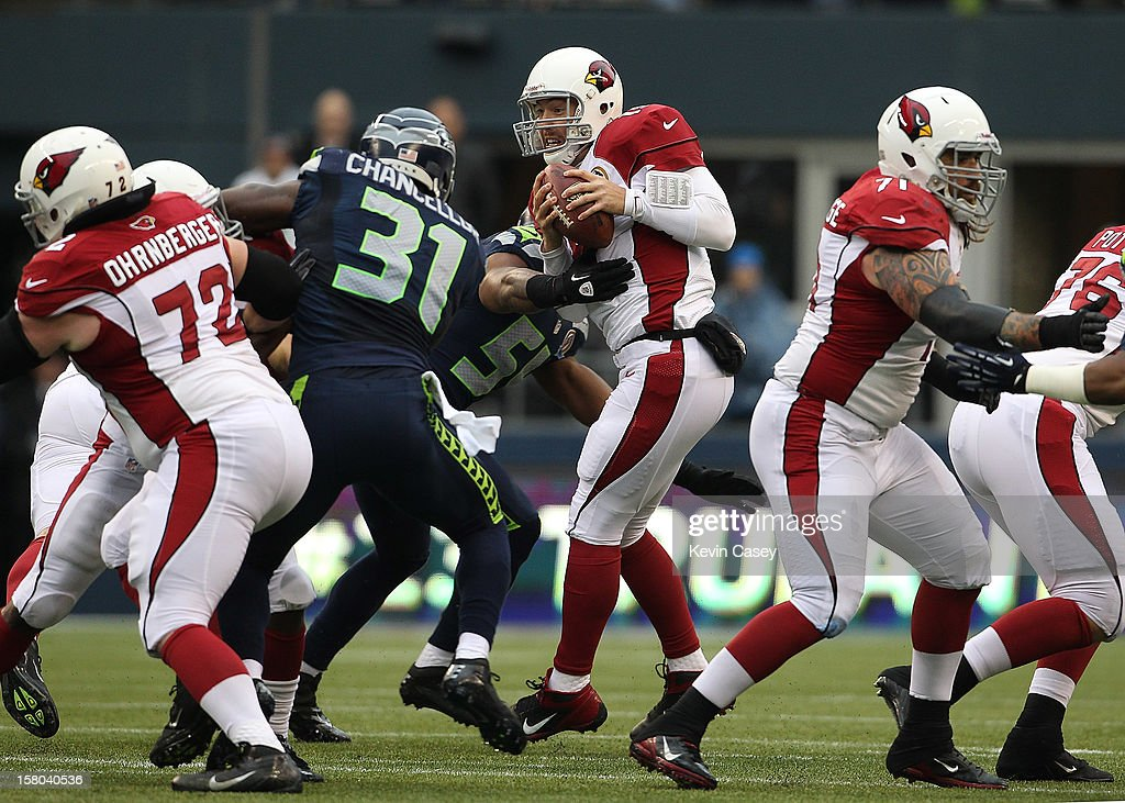 John Skelton #19 quarterback of the Arizona Cardinals holds onto the ball as he is swarmed by the Seattle Seahawks in the first half at CenturyLink Field on December 9, 2012 in Seattle, Washington.