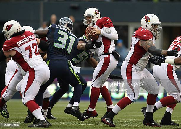 John Skelton quarterback of the Arizona Cardinals holds onto the ball as he is swarmed by the Seattle Seahawks in the first half at CenturyLink Field...