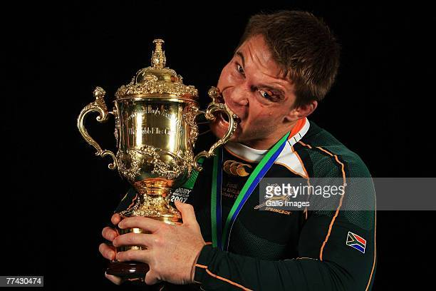 John Smit of South Africa bites the trophy following his team's victory at the end IRB 2007 Rugby World Cup final match between South Africa and...