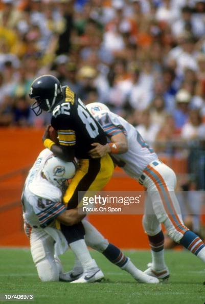 John Stallworth of the Pittsburgh Steelers is tackled by Glenn Blackwood and Mike Kozlowski of the Miami Dolphins during an NFL football game at The...