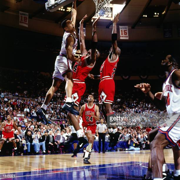 John Starks of the New York Knicks drives to the basket hard for a slam dunk over Horace Grant and Michael Jordan of the Chicago Bulls as Bill...
