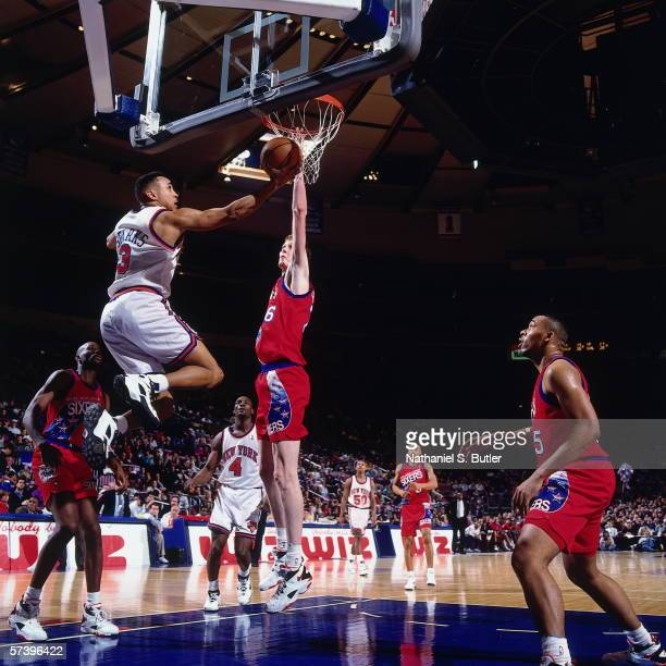John Starks of the New York Knicks shoots a layup against Sean Bradley of the Philadelphia 76ers during a game at Madison Square Garden on January 23...
