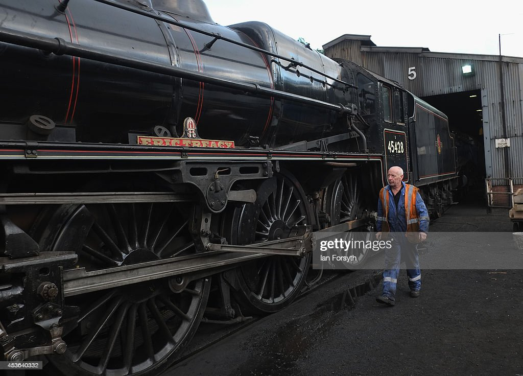 John Steels walks alongside the locomotive 'Eric Treacy' at Grosmont train engine sheds in preparation for the ceremony to mark a second platform opening at Whitby train station on August 15, 2014 in Whitby, England. The second platform will provide passengers with more options for travel to the Yorkshire seaside town on the North Yorks Moors Railway and was the first time in half a century two steam locomotives were side by side at the station.