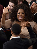 John Stephens aka John Legend gives a high five to Oprah Winfrey after winning the Best Original Song Award for 'Glory' from 'Selma' during the 87th...