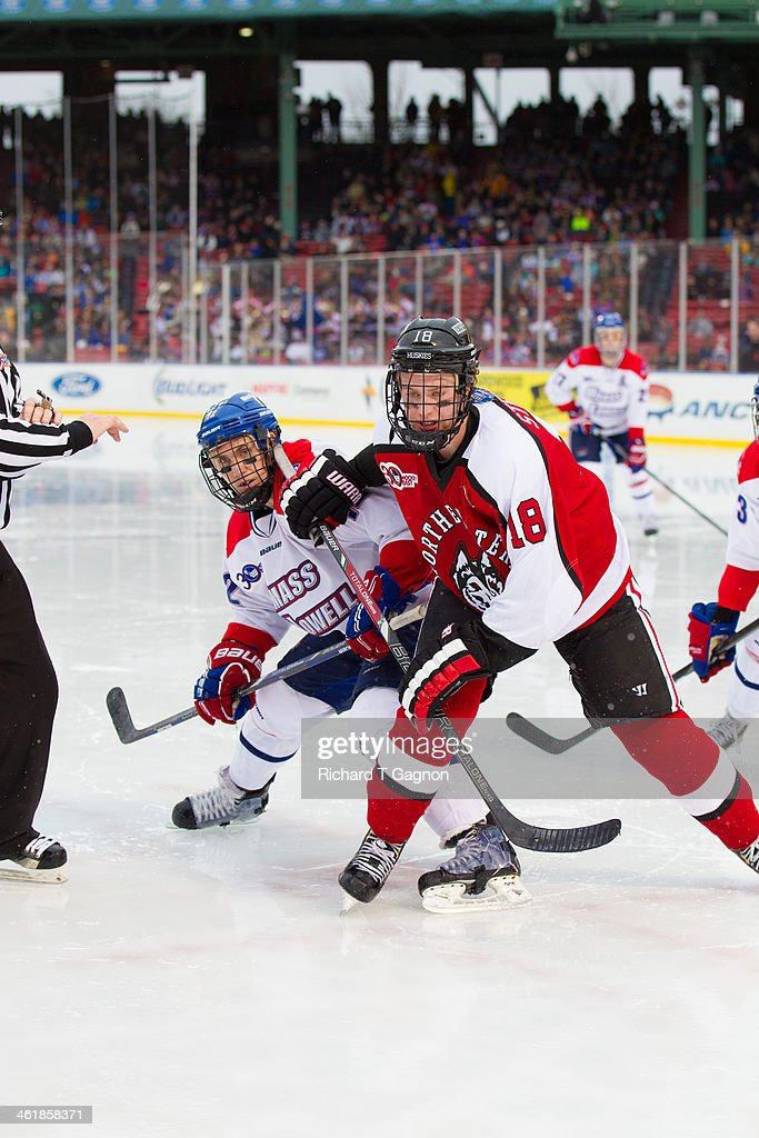 John Stevens #18 of the Northeastern University Huskies battles Josh Holmstrom #12 of the Massachusetts Lowell River Hawks during NCAA hockey action in the 'Citi Frozen Fenway 2014' at Fenway Park on January 11, 2014 in Boston, Massachusetts.
