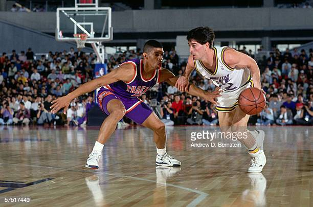 John Stockton of the Utah Jazz drives against Kevin Johnson of the Phoenix Suns during the 1990 Japan Games at the Tokyo Metropolitan Gymnasium in...
