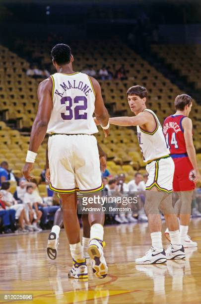 John Stockton of the Utah Jazz matches up with teammate Karl Malone against the Philadelphia 76ers during a game at the Vivint Smart Home Arena in...