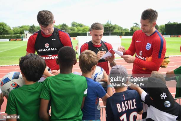 John Stones Kieran Trippier and Tom Heaton sign autographs during the England training session at Stade Omnisports on June 11 2017 in Paris France