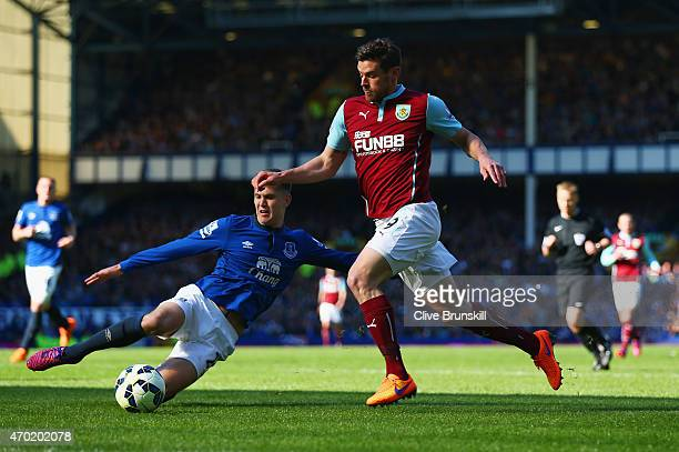 John Stones of Everton slides in to challenge Lukas Jutkiewicz of Burnley during the Barclays Premier League match between Everton and Burnley at...