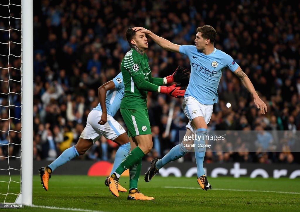 John Stones of Manchester City congratulats Ederson of Manchester City after saving a penalty during the UEFA Champions League group F match between Manchester City and SSC Napoli at Etihad Stadium on October 17, 2017 in Manchester, United Kingdom.