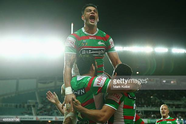 John Sutton of the Rabbitohs celebartes with Greg Inglis and Alex Johnston of the Rabbitohs after Johnston scored a try only to have it disallowed on...