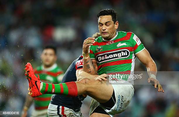 John Sutton of the Rabbitohs is tackled as he kicks during the round 26 NRL match between the Sydney Roosters and the South Sydney Rabbitohs at...