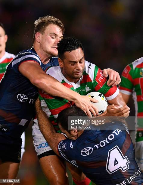 John Sutton of the Rabbitohs is tackled by Kane Linnett and Coen Hess of the Cowboys during the round five NRL match between the North Queensland...