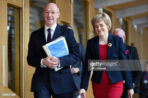 John Swinney Scotlands finance secretary and Deputy First Minister Nicola Sturgeon walk to the chamber where he outlined his budget plan for 201516...