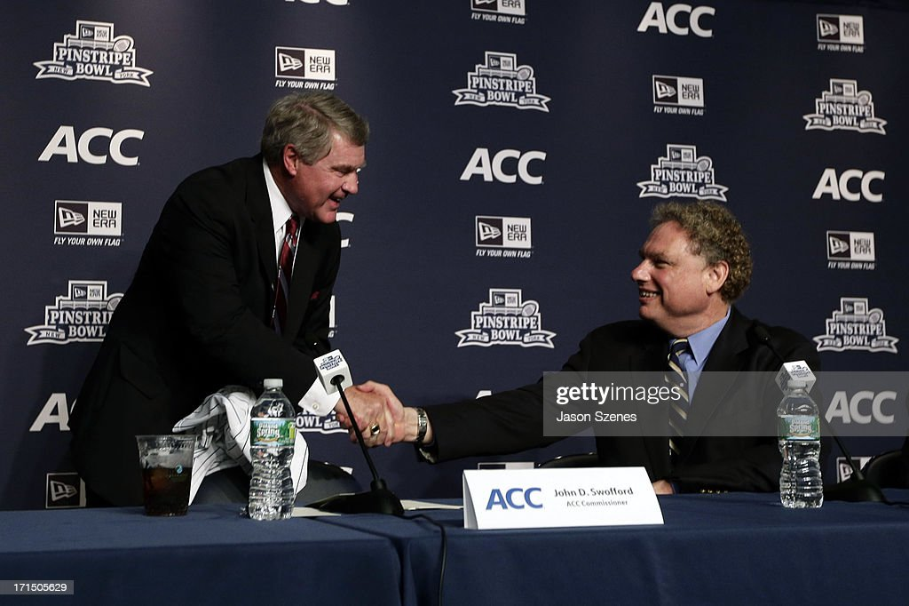 John Swofford, ACC Commissioner (L) shakes hands with Randy Levine, President of the New York Yankees after addressing the media during a press conference to announce the New Era Pinstripe Bowl's multi-year partnership with the Atlantic Coast Conference at Yankee Stadium on June 25, 2013 in the Bronx borough of New York City.