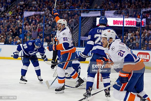 John Tavares and Kyle Okposo of the New York Islanders celebrate a goal as Nikita Nesterov of the Tampa Bay Lightning reacts during the first period...
